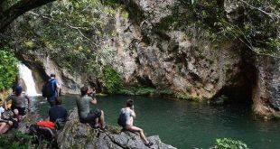 Tourists take photos of the Caburni Waterfall, in Topes de Collantes, Trinida de Cuba