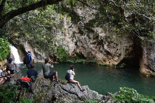 Tourists take photos of the Caburni Waterfall, in Topes de Collantes, Trinida de Cuba