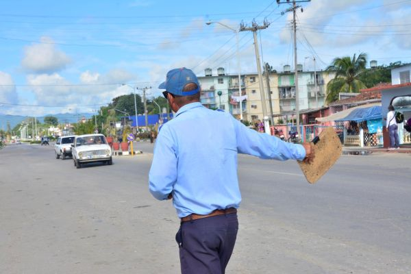 A traffic inspector waves at a car in order to make it stop