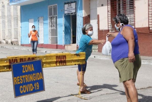 A woman hands over supplies to someone in a restricted area