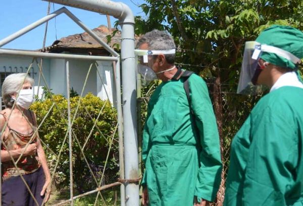 Two health workers stand outside a house to do the corresponding daily survey