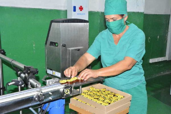 A female worker organizes minidose packages of honey for commercialization