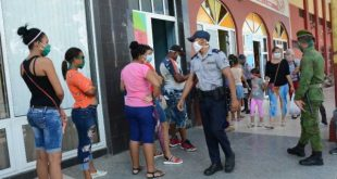 police officers watch the discipline of people who are standing in line outside a cafeteria in sancti spiritus, cuba