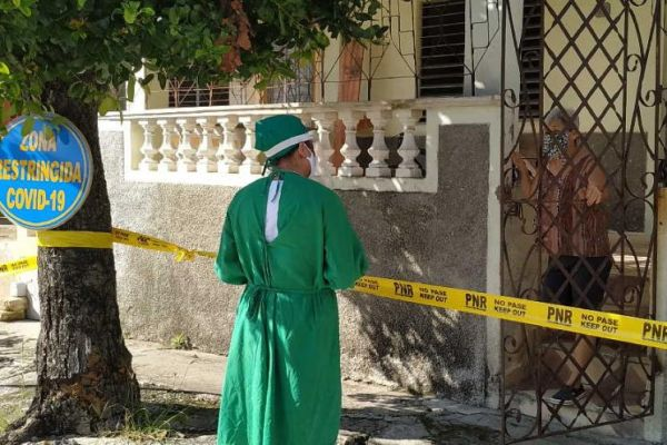 A health worker stands outside a house marked with a yellow ribbon to do the corresponding daily survey