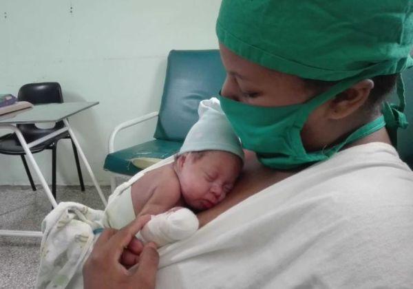 A mother holds her child after nursing him