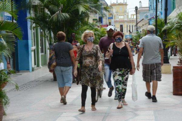 People walking along the Boulevard Street of Sancti Spiritus, all of them wearing face masks